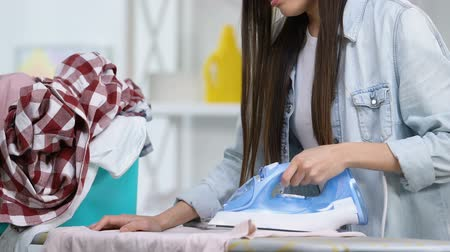 sıkıcı iş : Tired housewife ironing clothes, clothing face with hands and crying, hard work Stok Video