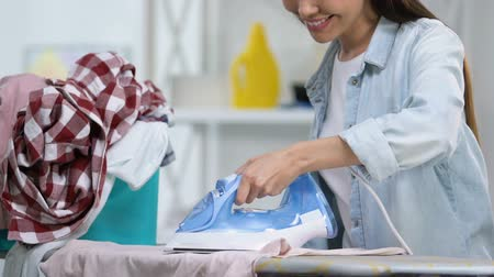 lavanderia : Cheerful housewife in good mood ironing t-shirt, enjoying domestic work, closeup