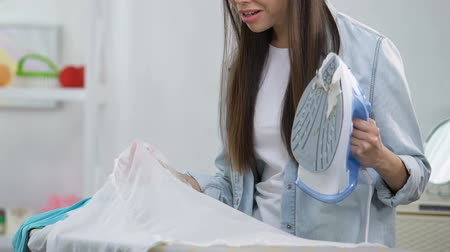 sıkıcı iş : Unexperienced female making hole in blouse during ironing, house work problems