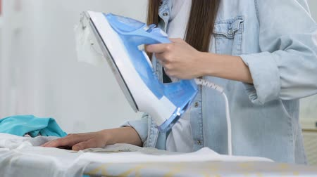 sprzątanie : Shocked woman making hole in blouse during ironing process, lack of experience