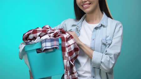 гладильный : Happy housewife holding basket with clothes and smiling at camera, laundry