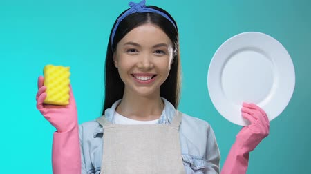 advert : Smiling housewife showing sponge and clean plate into camera, dishwashing