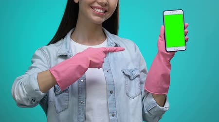 sprzątanie : Smiling housewife in gloves pointing finger into smartphone with green screen Wideo