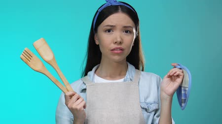 sıkıcı iş : Confused housewife holding kitchenware shrugging shoulders, lack of experience Stok Video