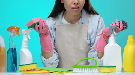 dezenfekte etmek : Confused housewife with sponge and detergents on table making decision, tips Stok Video