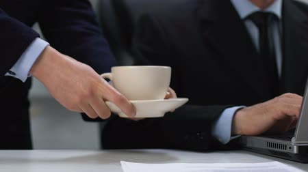 assistent : Female secretary serving coffee cup for male director working laptop, assistance
