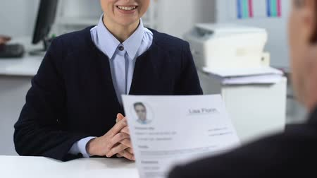 прокат : Male manager reading cv female job applicant, smiling woman looking interviewer Стоковые видеозаписи