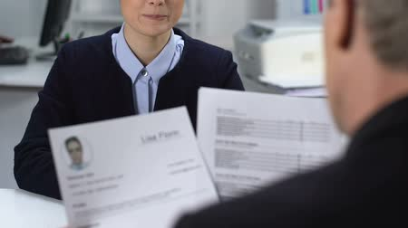 прокат : Female job candidate feeling nervous during interview, male manager reading cv