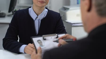 experiência : Male businessman interviewing young pretty woman suit, marking applicant resume