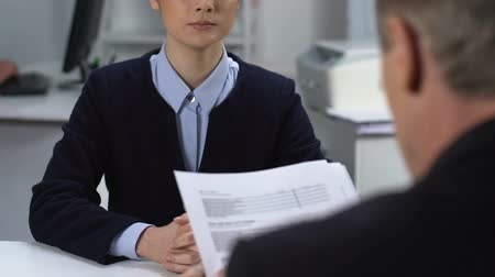 учет : Female office worker giving stack of documents to male manager, office paperwork