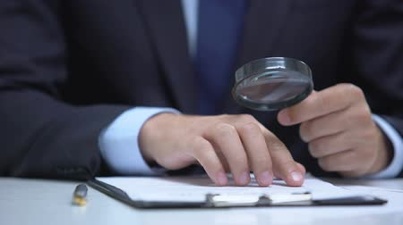 контракт : Attorney reading document with magnifier, studying case in detail, investigation