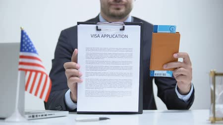 official : US consular officer showing visa application and passport, legal immigration Stock Footage