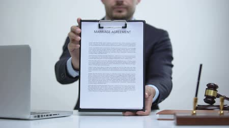 konsultant : Male attorney holding marriage agreement, family law governs marital property Wideo