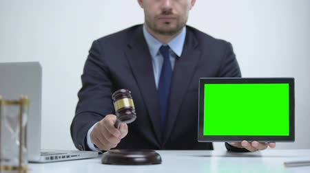 digital code : Lawyer pounds gavel on block, holds tablet green screen, attorney service online