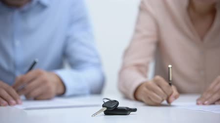 gerechtigheid : Car keys closeup, couple signing divorce documents about property division Stockvideo