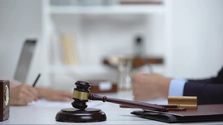 судья : Gavel and block on table, woman meeting lawyer on background, notarial services