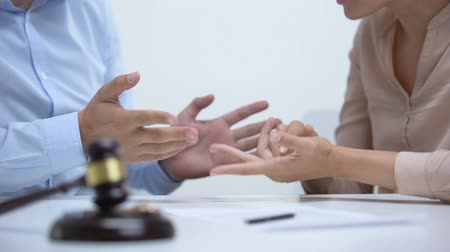 gerechtigheid : Spouses arguing about property division during divorce, gavel and rings closeup