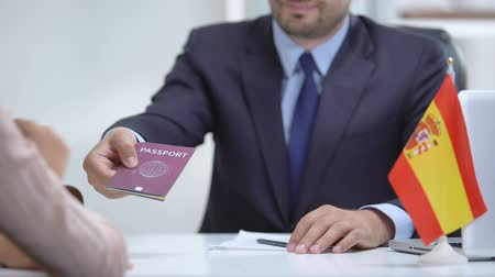 registration : Spain consular officer giving passport to immigrant, work visa, citizenship