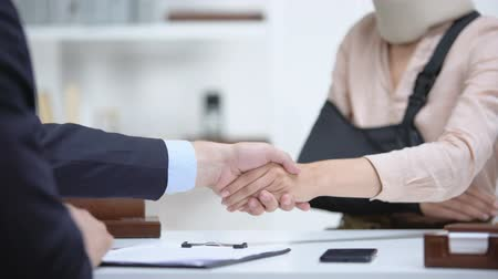acidente : Insurance agent shaking hand with woman in arm sling, psychological support