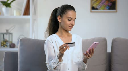 acheter : Smiling female entering credit card number in smartphone, money transfer service Vidéos Libres De Droits