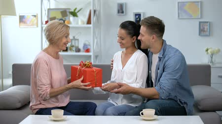 convidado : Couple presenting red giftbox to mother-in-law, family relationship, anniversary Vídeos