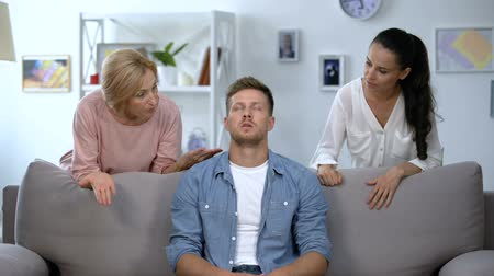 аргумент : Irritated man sitting on sofa, listening wife and mother reproach, problem