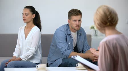 confronto : Offended couple sitting on sofa in psychologist appointment, reconciliation Stock Footage