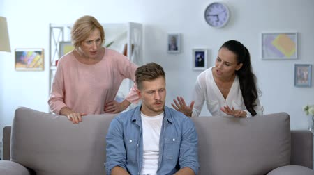 аргумент : Tired man sitting on sofa, enduring to wife and mother criticize him, quarrel
