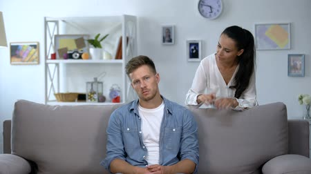 milující : Phlegmatic man sitting on sofa listening nervous wife shouting, aggression