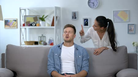 gesticulando : Nervous woman criticizing lazy husband sitting on sofa, family conflict, problem Vídeos