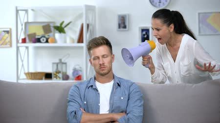 divorzio : Woman with megaphone shouting on man at home, unsuccessful marriage, conflict Filmati Stock