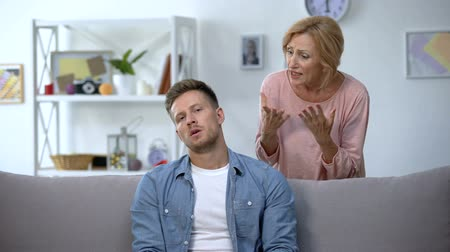 agresif : Disappointed mom talking to lazy adult son sitting on sofa at home, upbringing