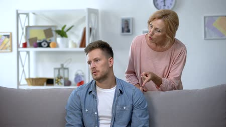 milující : Nervous mother talking to adult son sitting on sofa at home, family conflict Dostupné videozáznamy
