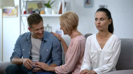convidado : Husband talking with mother at home, not paying attention on offended wife
