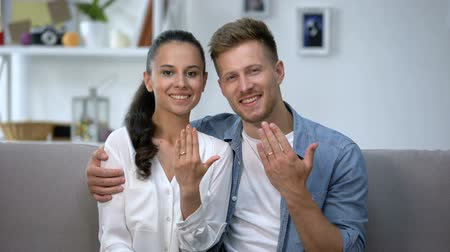 preziosi : Cheerful couple sitting on sofa, showing hands with engagement rings, love