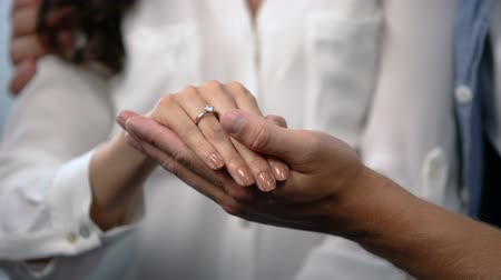 fiancee : Man tenderly holding fiancee hand with engagement ring, future family, love