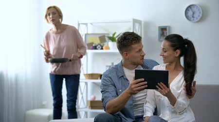 любопытство : Curious mother-in-law looking young couple scrolling on tablet PC at home Стоковые видеозаписи