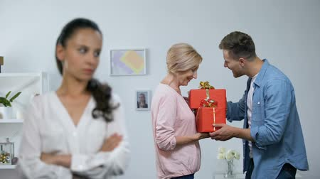 lack : Upset woman with hands crossed, husband presenting gifts to mother, attention