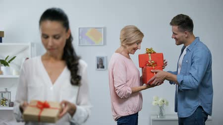 чувствовать : Woman looking at small gift box, while husband giving mother big presents Стоковые видеозаписи