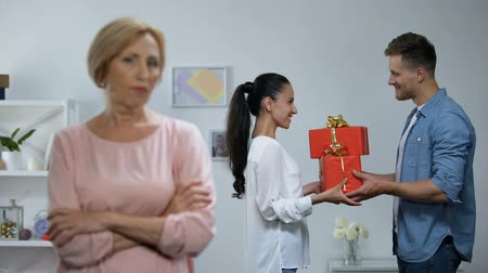 zamilovaný : Displeased mother-in-law looking her son presenting gifts to wife, jealousy