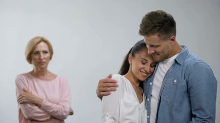 proti : Offended mother-in-law looking at couple tenderly hugging, lack of attention