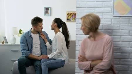 jealous : Jealous mother-in-law watching young couple hugging at home, unwanted relations