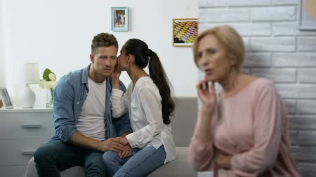 dialog : Curious mother-in-law secretly listening woman whispering secret on husband ear Wideo