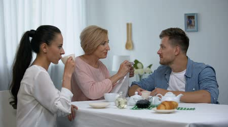 mãe : Shocked wife looking at mother-in-law putting napkin on husbands neck, tea party