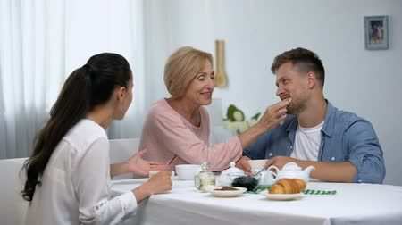 çay : Angry wife arguing with mother-in-law wiping sons mouth during coffee break