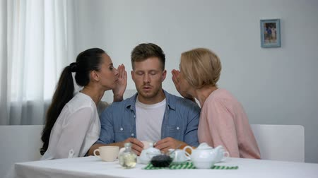 proti : Irritated man listening wife and mother-in-law whispering on ear, problems