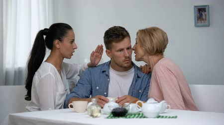 jealous : Man listening wife and mother-in-law whispering on ear, choosing mom advice