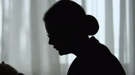 отчаянный : Silhouette of tired woman holding head, overworked and depressed, closeup