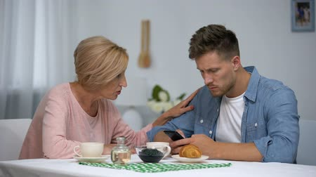 przyszłość : Worried mother talking to infantile adult son playing video games on smartphone