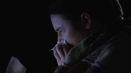 noc : Sick girl wrapped in blanket sneezing suffering seasonal influenza, closeup